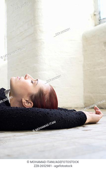 Woman with eyes closed laying down on the floor