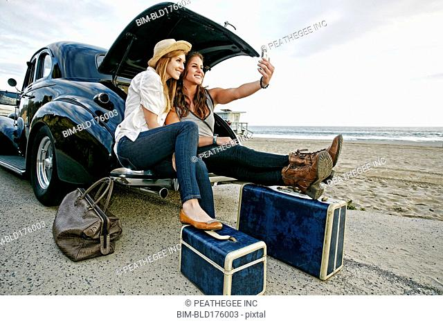 Women with luggage and vintage car on beach