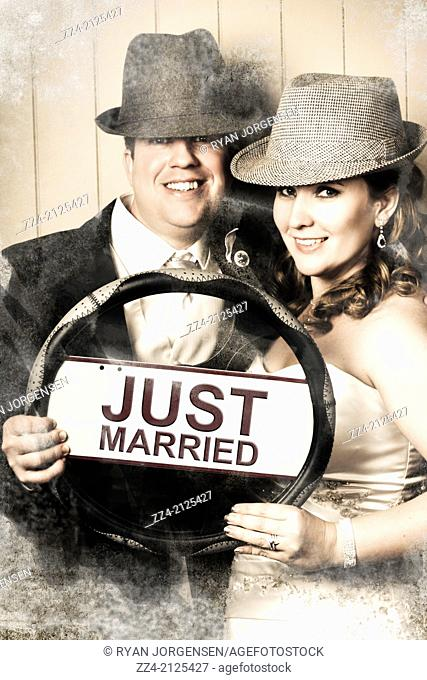 Vintage picture of a cute bride and groom holding the wedding car steering wheel with just married number plate wearing vintage fedora hats when heading on...