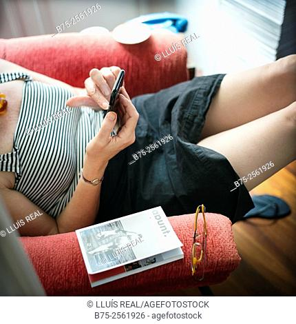 Woman sitting in a red armchair, in a relax position, handling a mobile phone in a town house. Mahón, Menorca, Balearic Islands, Spain, Europe