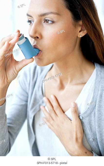 MODEL RELEASED. Young woman using an inhaler with her hand on her chest