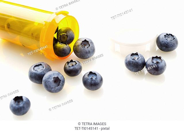 Blueberries spilling from prescription bottle