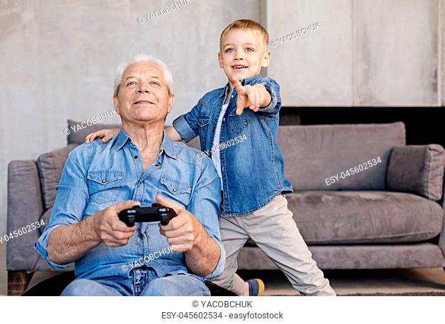 Now turn left. Two hilarious passionate men using special controller for playing while his grandchild guiding him through the process