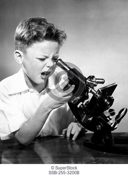 Schoolboy looking through microscope