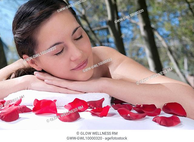 Woman lying on a massage table with rose petals in front of her