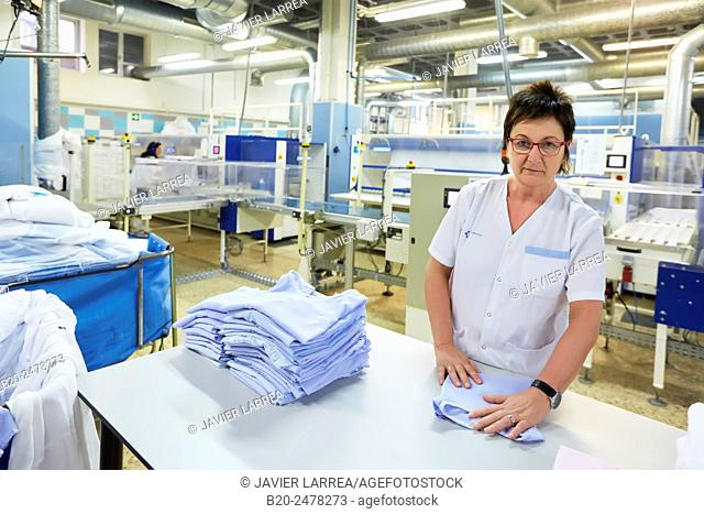 Woman classifying and folding clothes at hospital laundry, Hospital Donostia, San Sebastian, Basque Country, Spain
