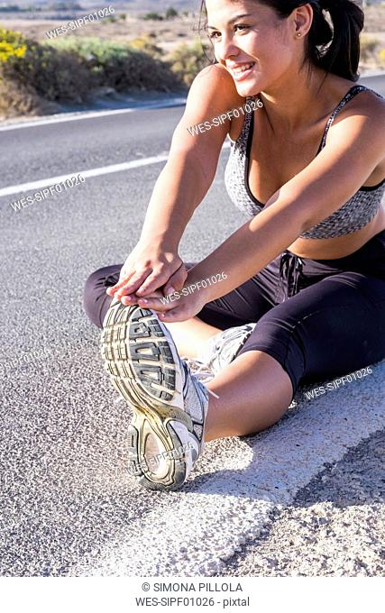 Young woman doing stretching exercises on an empty road