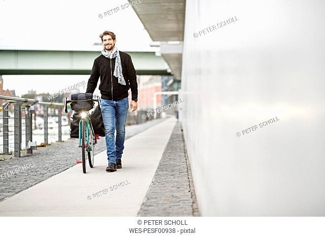 Smiling man pushing bicycle on a path