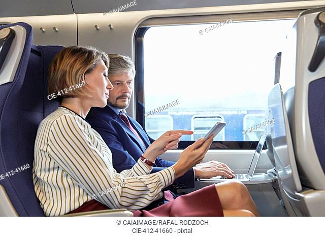 Businessman and businesswoman working, using digital tablet on passenger train