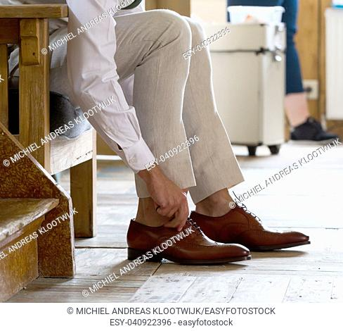 Man in a business suit ties the laces - Selective focus