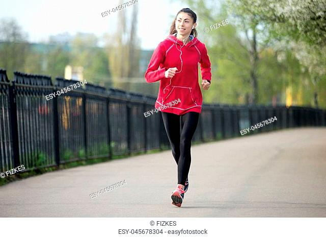 Portrait of smiling beautiful female running in park during everyday practice. Fitness woman jogging outdoors and listening music