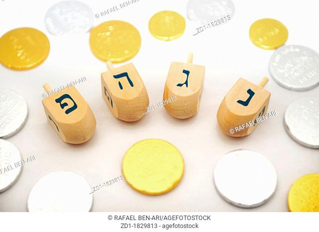 Photo of dreidels spinning tops and gelts candy coins for Hanukkah isolated on white