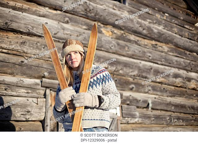 Portrait Of A Young Woman Holding Wooden Skis By A Log Cabin; Homer, Alaska, United States Of America