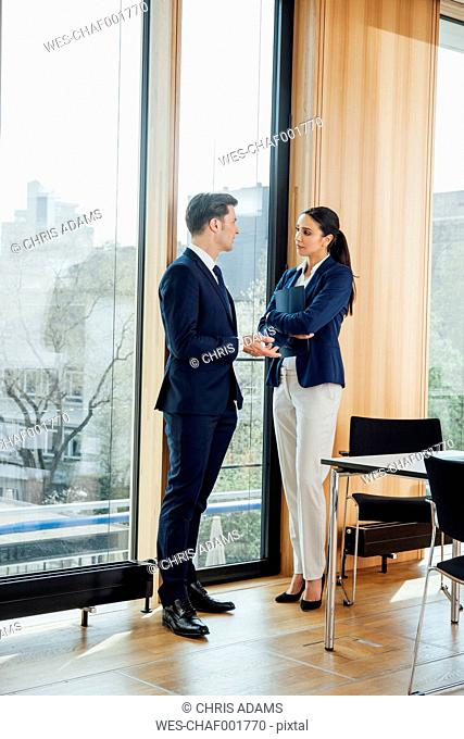Businessman and businesswoman in office talking at the window