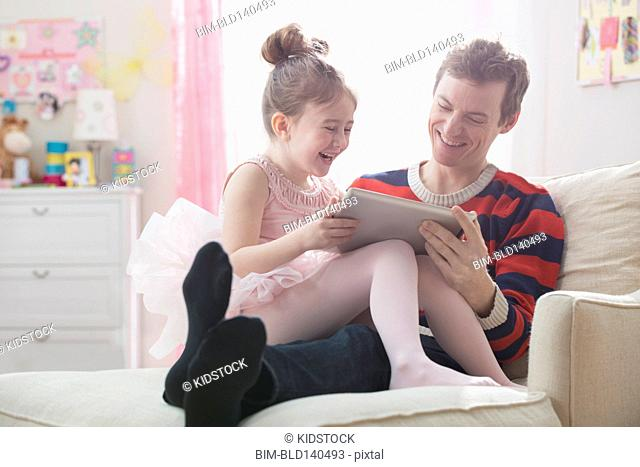 Caucasian father and daughter using digital tablet in bedroom