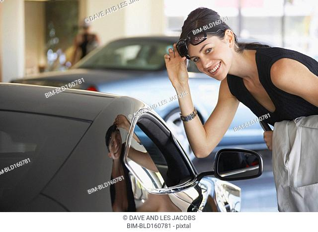 Caucasian woman examining sports car for sale in dealership