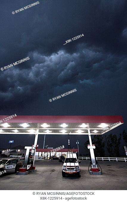 A Project Vortex 2 storm chaser waits out a squall line beneath a gas station awning in Nebraska, May 24, 2010
