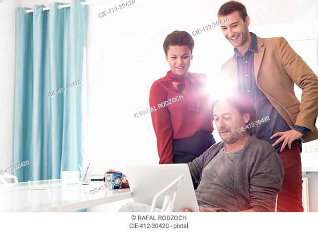 Business people sharing laptop in office meeting