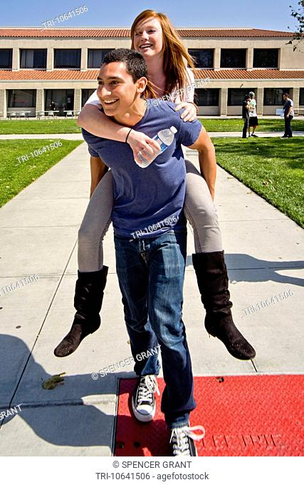 A Hispanic student carries his Caucasian girlfriend piggyback across the campus of Saddleback College in Mission Viejo, CA