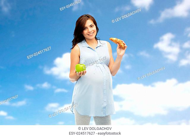 pregnancy, healthy eating, junk food and people concept - happy pregnant woman choosing between green apple and croissant over blue sky and clouds background