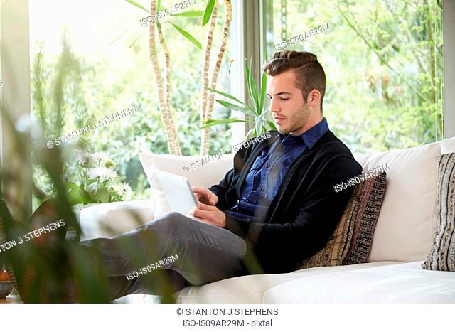 Man relaxing on sofa with feet up looking at digital tablet