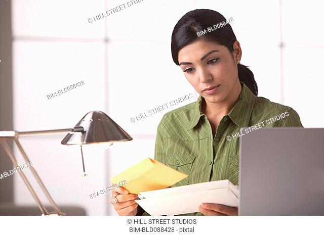 Hispanic woman looking at mail