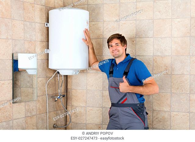 Portrait Of Smiling Technician Gesturing Thumbs Up In Bathroom