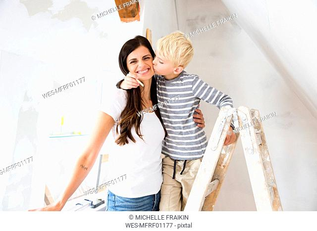 Portrait of happy mother and son working on loft conversion