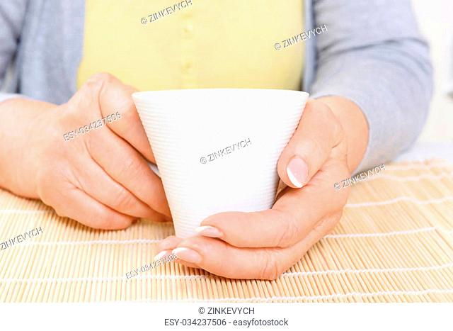 Taking rest. Portrait of white cup held by old lady in kitchen