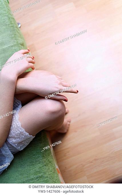 Caucasian female bare legs indoors on sofa