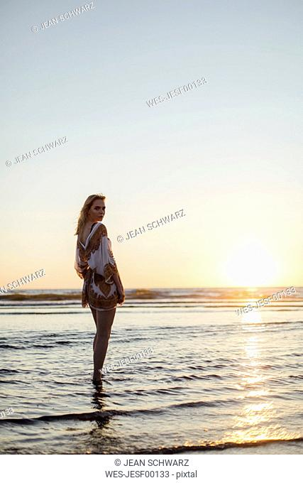 Portrait of a young woman standing in the sea at sunset