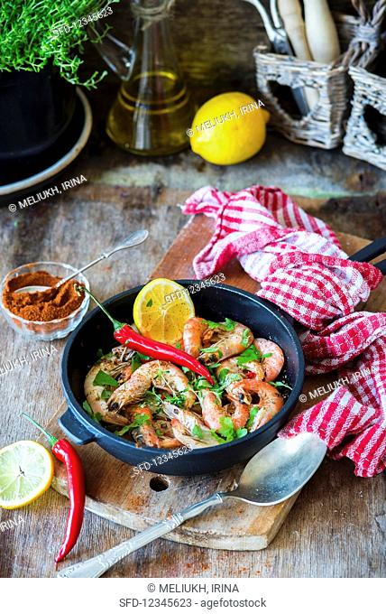 Fried spicy prawns with herbs in a pan