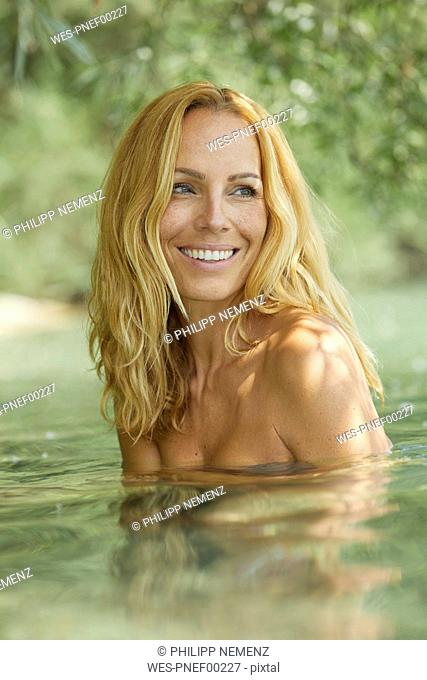Portrait of laughing blond woman bathing in lake
