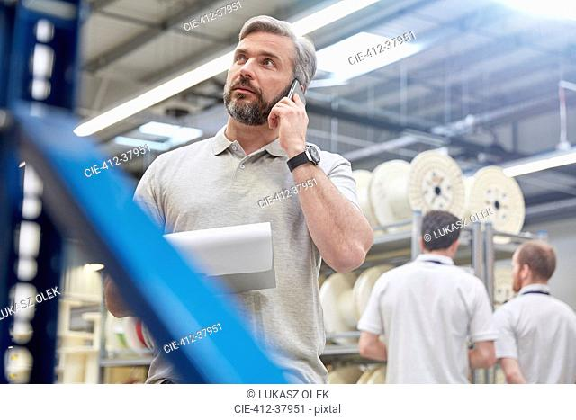Male supervisor with clipboard talking on cell phone in fiber optics factory