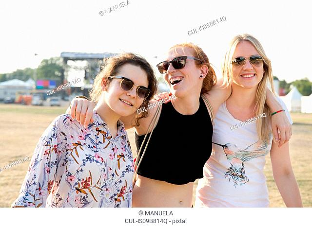 Portrait of three female friends at festival, smiling