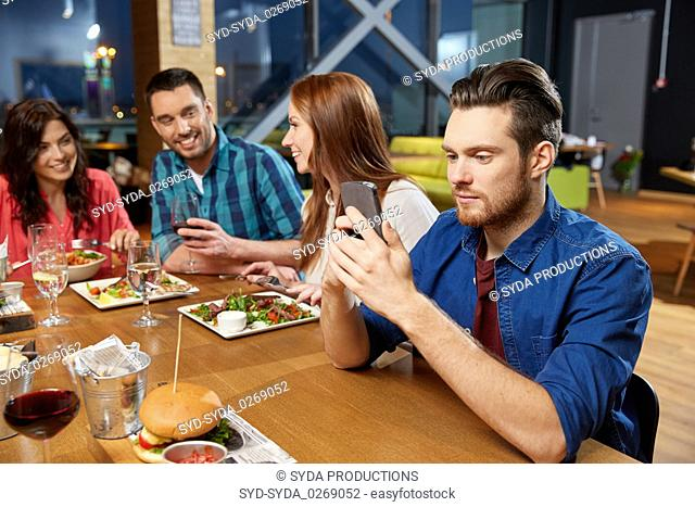 man messaging on smartphone at restaurant