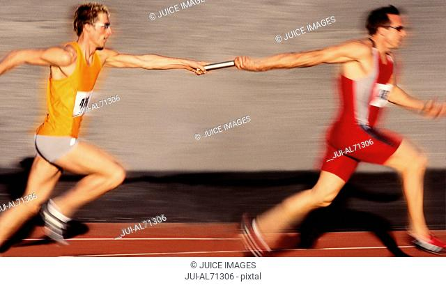 Blurred view of an athlete handing a flag to another athlete in a race