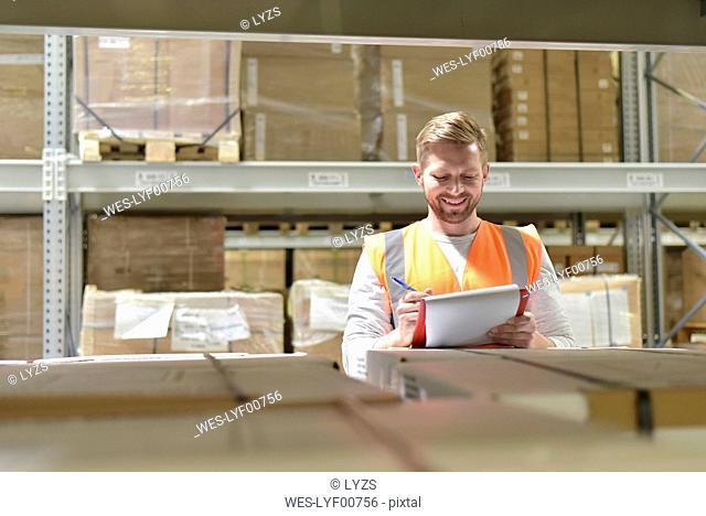 Smiling man in factory hall wearing safety vest holding clipboard