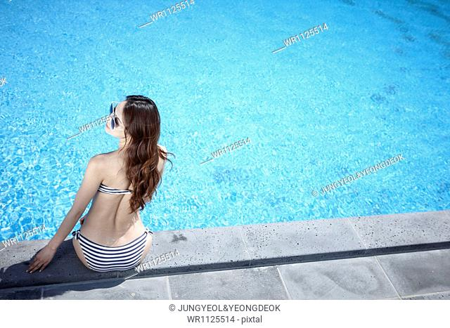 a woman sitting next to the pool