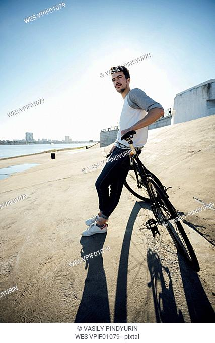 Young man with commuter fixie bike having a break at concrete wall