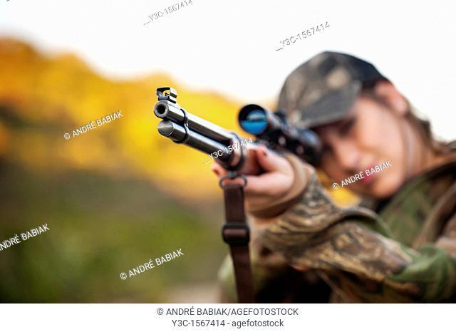 Hunting Season - Female hunter shooting firearm gun