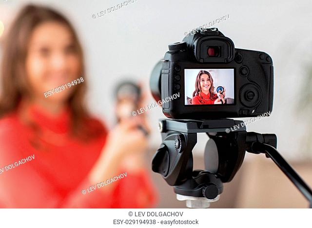 blogging, technology, videoblog, makeup and people concept - happy smiling woman or beauty blogger with bronzer, brush and camera recording tutorial video at...