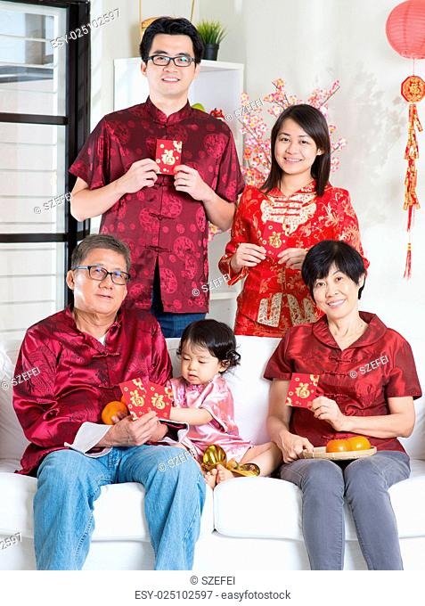 Celebrating Chinese new year. Happy Asian multi generations family in red cheongsam showing red packets while reunion at home