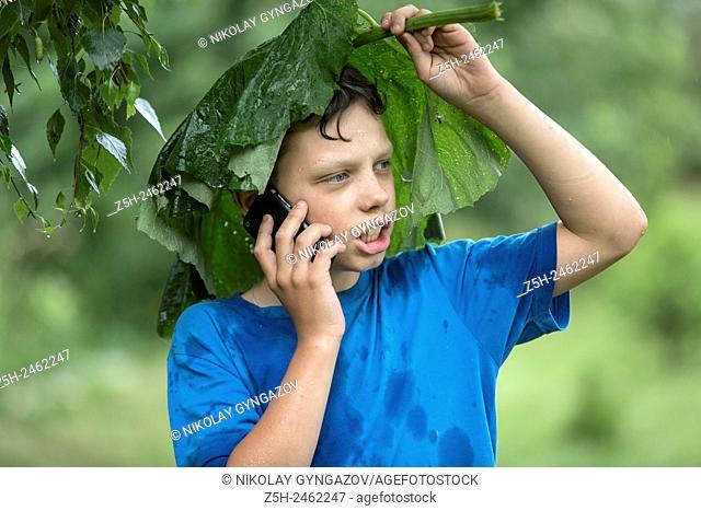 Russian Federation. Belgorod region. The boy in the rain uryvshiysya leaves of the plant