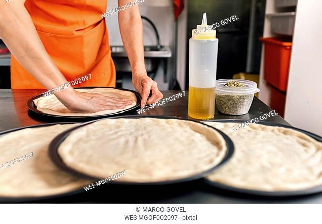 Woman's hands preparing pizza dough, partial view