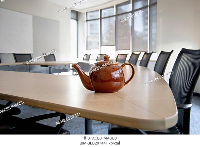 A brown china teapot on boardroom table in empty boardroom