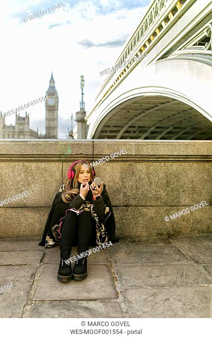 UK, London, young woman listening music and painting her lips near Westminster Bridge