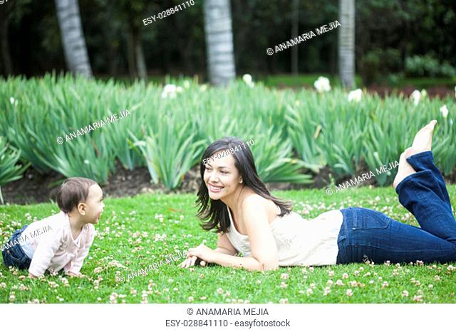 Baby girl playing with her mom on the grass