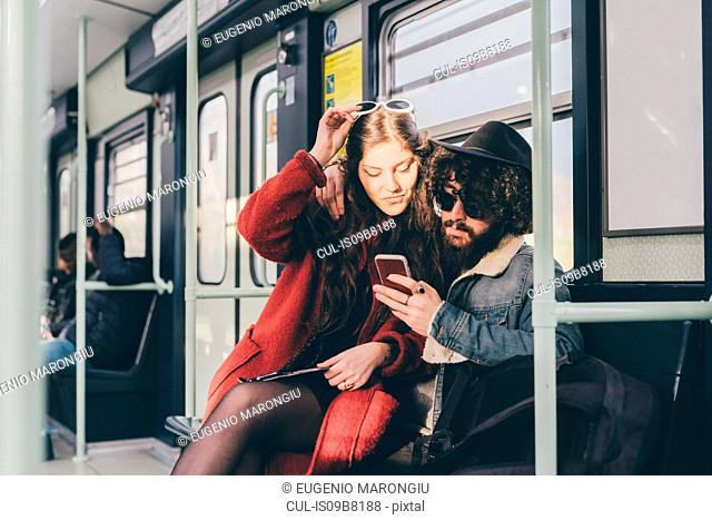 Young couple sitting on subway train, looking at smartphone