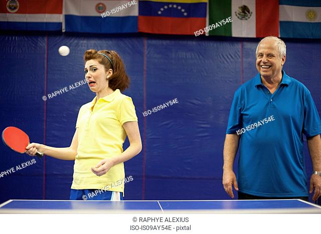 Table tennis coach laughing at student playing